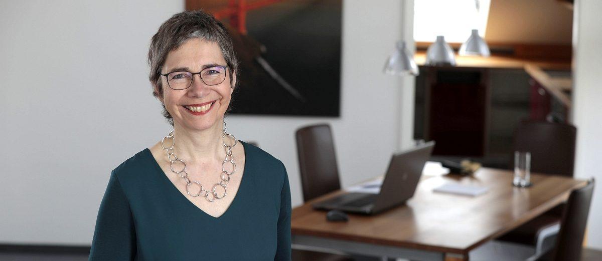 Susanne Schmidt-Lüer, Journalistin, steht vor einem Tisch mit aufgeklapptem Laptop